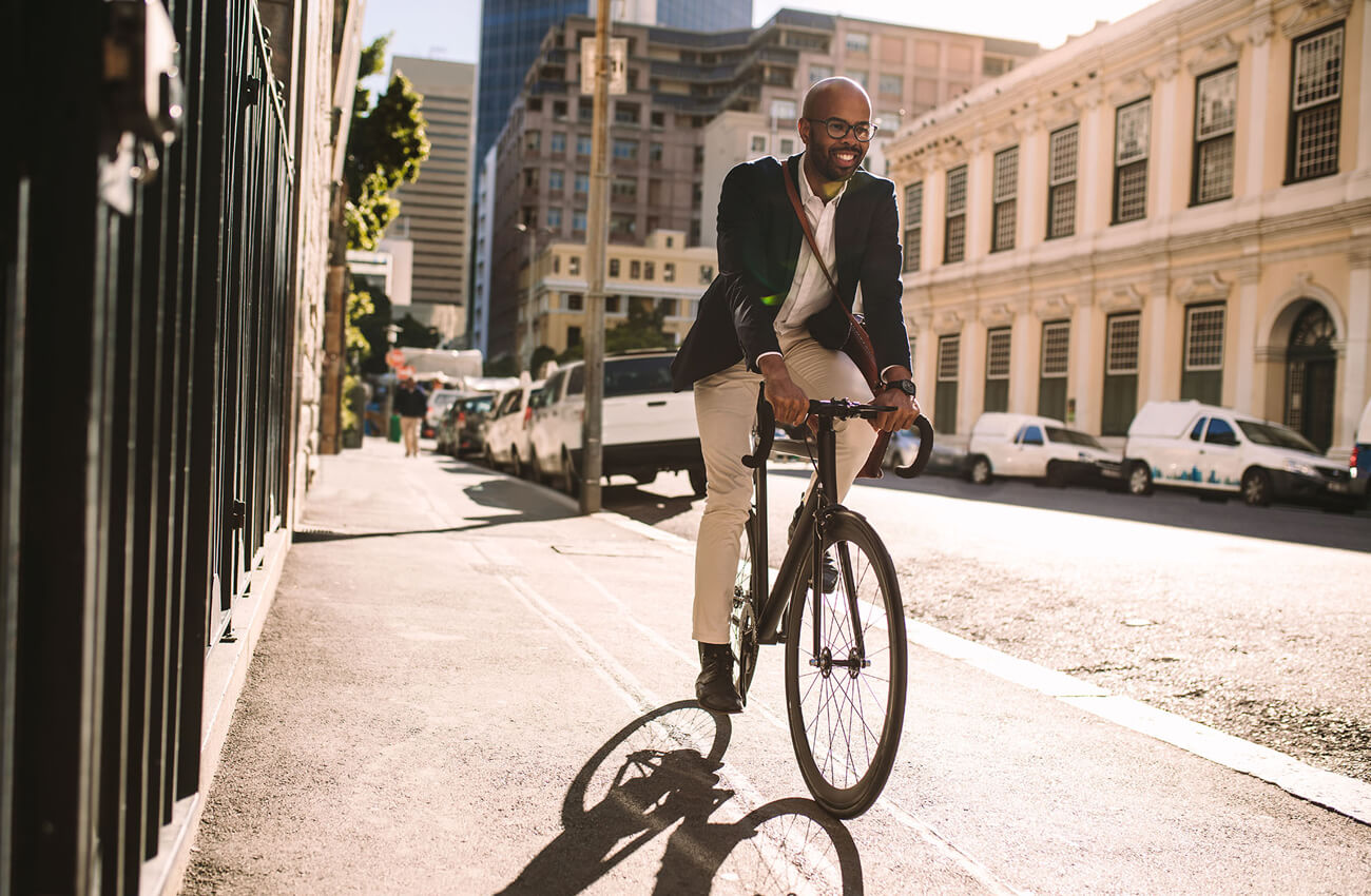 Smiling businessman cycling to work